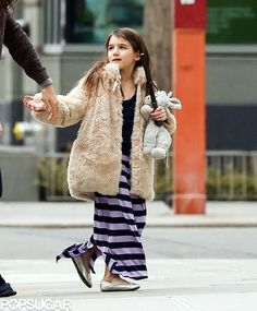 Suri Cruise accessorized her striped maxi skirt and fur coat with her stuffed animal.