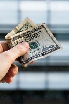100 dollar bill in hand closeup by Sonja Lekovic for Stocksy United