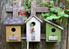 Series of three bird houses attached to a wooden fence.