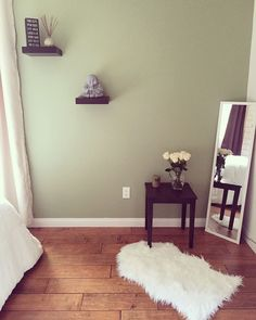 Zen Style Bedroom. Sage green wall paint, Buddha accessory, white roses.