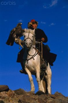 Golden Eagle (Aquila chrysaetos) and Kazakh on horse at second annual eagle festival, Mongolia