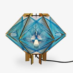 Andromeda Star Table Lamp-The Andromeda Lighting Series is part sculpture and part lamp. Intricately woven string criss crosses between a wooden frame making colorful geometric patterns. Inspired by mid-century modern lighting, string art and tensegrity sculptures, these lamps will turn heads whether they are on or off. With endless color combinations we are able to create you a one-of-kind lamp for your home.