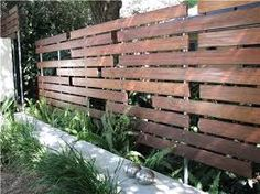 Fences don't have to be solid. This fence has openings that let light through and reveal greenery behind, while still providing plenty of privacy from the neighbors. The random horizontal arrangement of the boards along with the visible metal posts and fasteners creates a modern look.