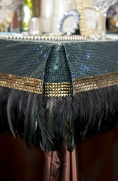 Custom sequin table cap with black pheasant feathers, gold spikes and inverted pleats in the corners.