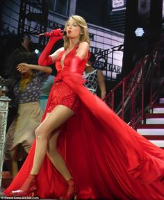 Taylor Swift wearing a red cape dress for her performance at the O2 in London as part of her RED tour. Taylor could not help but show off her enviable, long legs in the outfit