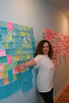 """Laurell K. Hamilton posing in front of her Sticky Note wall. Many writers use these or index cards to plan out their book plots."""