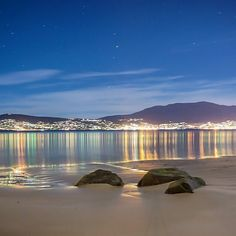 The lights of Hobart reflected in the Derwent Estuary below kunanyi /Mount Wellington.