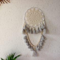 L'attrape-rêve ADAHI est composé d'un napperon ancien fixé sur un  cercle recouvert de laine de 24cm.Il est ensuite agrémenté de 7 pompons en mélange de laine et coton beige et gris fixés directement sur le cercle, puis d'une composition de pompons espacés de perles de bois brut (10mm) et bois peint blanc (8mm). Deux dernier pompons sont fixés de chaque coté, et une plume d'oie blanche vient finir le tout.La couleur des pompons peut être modifiée sur demande ...