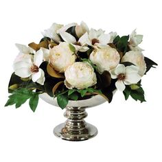 """Faux white magnolia and green leaf arrangement in a basket planter.  Product: Faux floral arrangementConstruction Material: Polyester, plastic, and metalColor: White and silverDimensions: 17"""" H x 20"""" DiameterCleaning and Care: Dust with dry cloth"""