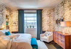 Ricorda quasi i motivi vegetali dell'art nouveau la caratteristica carta da parati della camera da letto matrimoniale. Cassettone vintage e pavimento in parquet