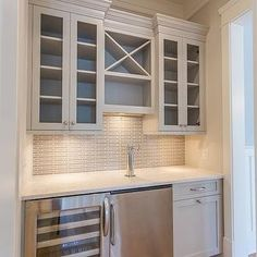 Kitchen - built in wet bar with stainless steel beverage fridge and glass front wine fridge. Speckled gray countertop, linear gray acksplash tile, gray backsplash tile, glass front upper cabinets, brushed nickel cabinet pulls, x front wine cubbies, x front wine storage, built in bar ideas.