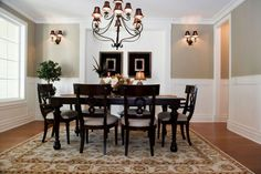 Stately black furniture stands out against the pale walls and area rug. The wrought iron spirals in the chandelier and matching sconce lighting adds a touch of almost gothic whimsey to this dining room.