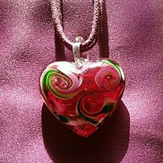 Glass heart necklace Heavy glass heart. It has swirls of green and white and mauve. Jewelry Necklaces