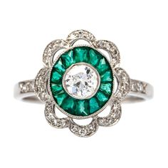 Emerald and Diamond Scalloped Art Deco Engagement Ring. Art Deco platinum set engagement ring centering a bezel set Old European Cut diamond gauged at 0.33ct graded H-I color and SI clarity and surrounded by a bright green halo of fourteen calibre cut emeralds totaling about 0.40ct. Mount Vernon is further decorated with a scalloped halo of thirty-four single cut diamonds totaling approximately 0.15ct. Circa 1920s-1930s