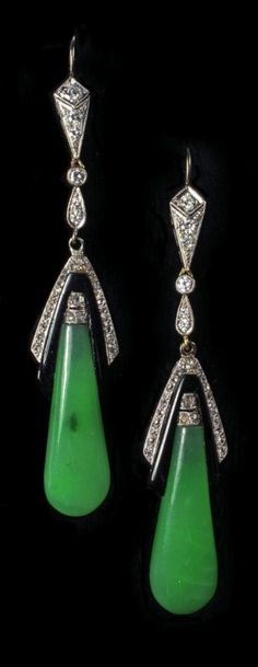 A pair of Art Deco jadeite, onyx and diamond ear pendants, 1920s. The elongated tear drop jadeite with geometric border of onyx and rose cut diamonds, below a diamond set shepherds crook wire fitting, mounted in unmarked white metal, approx 6.5cm long, in royal blue and black velvet fitted case/stand.