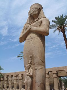 EGYPT: The dimunitive figure of a graceful Queen Nefertari standing between the legs of the colossal granite statue of Ramesses II, in the first courtyard of the Temple at Karnak.
