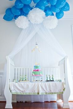 "Dessert Table: ""To carry out the theme, a sleigh crib with a coordinating crib skirt was used as the dessert table,"" Christine says. ""White canopy netting, pom pom clouds, and two dozen sky blue balloons created a dreamy effect."""