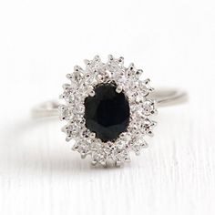 Stunning vintage 18k white gold ring featuring a 1 CT oval cut genuine sapphire! The ring is further detailed with a double halo of 28 single cut diamond accents. The center sapphire gemstone is a lovely very dark grayish violetish blue, and secured with 4 prongs. The sparkling diamond