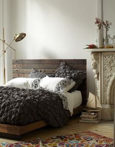 Texture. Wood bed frame, dark linens, and bright rug.