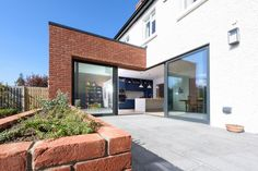 Changes to the internal layout and a small brick-clad extension made a huge impact on the workings and space in this home.  Sliding doors open from a corner to expand the living spaces into a landscaped terrace beyond.