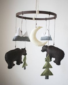 A beautiful handmade mobile that is the perfect addition to any Woodland themed nursery. All mobiles are hand stitched and made to order for your little one. Each piece is drawn and designed by TwoEggsNesting, then made from felt and filled with polyester stuffing. Colors: Colors shown in picture are as follows- -Moon: Cream -Mounatins w/snowy tops: Grey with White -Trees: Grey Trunks, Olive Tree -Bear: Dark Brown *Custom colors available upon request. Please make note of colors want...