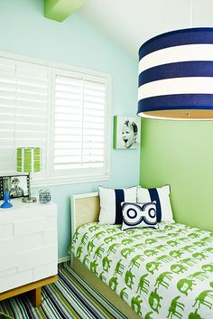Preppy Boys Bedroom - classic navy blue and Kelly green,  the stripe barrel shade  Change bedspread to feminine print in green, and paint headboard wall pale pink.