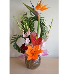 Tropical arrangement with bird of paradise, sago palm, pink dendrobiums, anthurium, roses and lily.