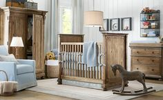 Nursery flush with natural wood materials, from dresser to high walled crib to wardrobe on left. Baby blue accents throughout: armchair, bedding, and changing table cushion.