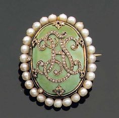 Gold and enamel brooch, set with a cabochon cut turquoise and pavé diamond monogram, within a pearl surround, late 19th century, weight: 17.60 g.