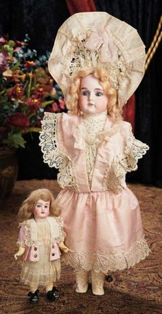 """Two All-Original German Bisque Child Dolls --9"""" (23 cm.) and 18"""". Each has bisque socket head, blue glass sleep eyes, painted lashes and brows, open mouth, four teeth, mohair wig, Sonneberg composition and wooden fully jointed body. Condition: generally excellent. Marks: Made in Germany 390 A 1/0 M (smaller). Comments: Marseille, circa 1890. Value Points: the pretty little girls are entirely original, wearing fancy store costumes, the larger with wire-framed bonnet to match the dress."""