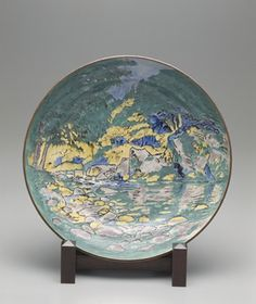Plate with Kutani-style landscape  mid 20th century    Kinoshita Yoshinori , (Japanese, 1898 - 1996)   Showa era     Porcelain with enamels over colorless glaze  H: 9.2 W: 41.3 D: 41.3 cm   Tokyo, Japan.  The two artists began using Kutani-style colors to render the pictorial subject matter of modern oil painting on porcelain.