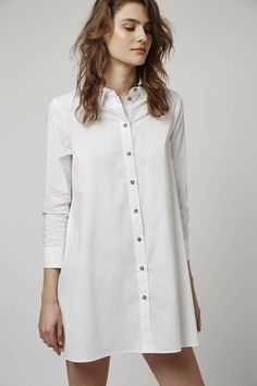 Look to minimalistic cool in this simple oversized shirt dress. Crafted in a rich cotton blend, it comes detailed with a crisp collar and exposed button detailing. Finished with hand pockets, we love it styled back with leather sliders for a casual feel. #Topshop