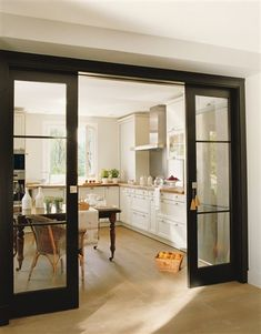 Instead of disappearing these pocket doors stand out with black paint, large panes and brass hardware.
