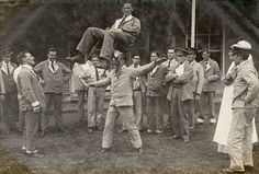 Staff and patients gather outside a Military Hospital in Basingstoke to watch two men engaged in a balancing act.  One man sits on a wooden chair which the other is holding in his teeth and supporting by a pad on his forehead.   HMCMS:DPAAOS09