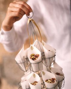 Parchment-paper packets, stamped with ferns, hold pistachios, a pre-ceremony snack; a waiter passes them out to guests in a wire egg holder.