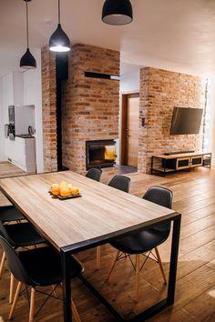 Czerwone cegły i kominek wzbogacają znacząco wystrój nowoczesnej jadalni. Bazowe drewno wprowadza ciepły klimat i naturalność do wnętrza. Jadalnię połączono z salonem, uzyskując jedną dużą i wygodną przestrzeń do codziennego użytkowania.