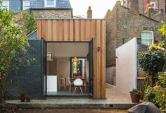 Larch cladding and black brick rear extension. Yoakley Road by Bradley Van Der Straeten Architects.