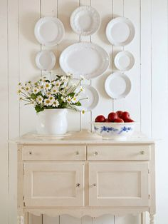 Welcoming Entrance. A antique buffet, dressed up with crystal knobs and lightly distressed ivory paint, welcomes guests and offers subtle tone-on-tone contrast in the farmhouse's crisp white entry