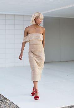 Street style look com vestido nude e sandália vermelha.