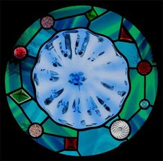 OCEAN THEME ROUNDEL WINDOW : A vague shell wave pattern in the roundel and the variety of jewel shapes and colors represent diatoms which are beautiful glass like microscopic sea creatures.