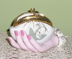 Hand holding a lily of the valley coin purse.