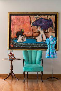 Decoração com personalidade, decoração colorida com obras de arte, piso de madeira, poltrona verde e luz natural.