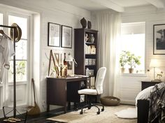 A corner in the bedroom with a brown desk and a high bookcase. Completed with a swivel chair with a white cotton cover.