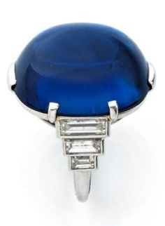 Mounted in platinum, adorned with an oval cut cabochon sapphire and six baguette diamonds, sapphire weighing approx. 34.04 ct, circa 1930. Signed Cartier.