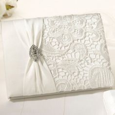 """This 8.5"""" cream lace guest book is beautifully crafted with an updated antique look. The cover is decorated with off-white lace, a cream satin sash and a rhinestone broach. This guest book has 55 two-"""