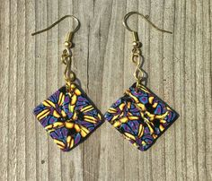 "Brilliantly colored 1-1/2"" dangle earrings with multicolored blue, black, purple and yellow abstract design. Square disk is 7/8"". Gold findings and hook style earrings.    ~ Handcrafted, one of a kind pieces    ~ Each item purchased is carefully packaged in organza gift bag    ~ Payment accepted: credit and debit cards, Etsy gift cards, Paypal    ~ See more items at www.etsy.com/shop/CatsUniqueBeads    ~ See more earrings at…"