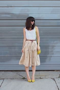 Classic and fun. Love the pops of yellow with this neutral midi skirt.