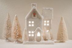 White glittered Christmas house and dyed bottle brush trees