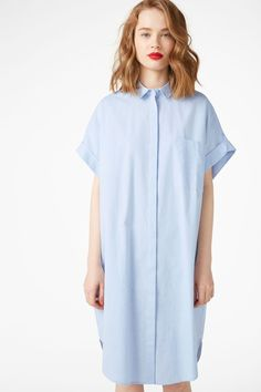 An oversized button-up shirt dress with a breast pocket, a rounded hemline and neat pockets hidden in the side seams.