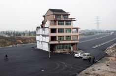 This picture taken on November 22, 2012 shows a half-demolished apartment building standing in the middle of a newly-built road thanks to a Chinese couple that refused to move in Wenling, in eastern China's Zhejiang province